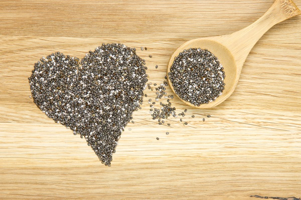 wooden spoon filled with black chia seeds and heart symbol